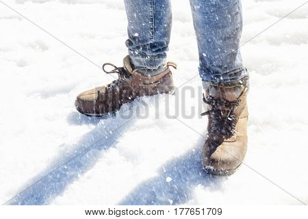 closeup of mans legs and shoes standing in the snow