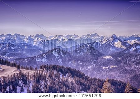 panoramic view of snowy mountains and forest with blue sky