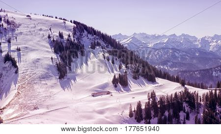 panoramic view of snowy landscape in the mountains with cottage