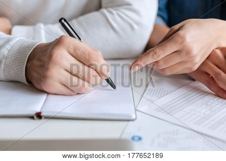 Taking notes. Close up of a pen being in hands of a nice handsome man while writing something in the notebook