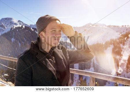 portrait of young man surrounded by snowy mountains is looking into the distance