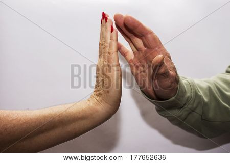 A female hand and male hand giving each other a high five.