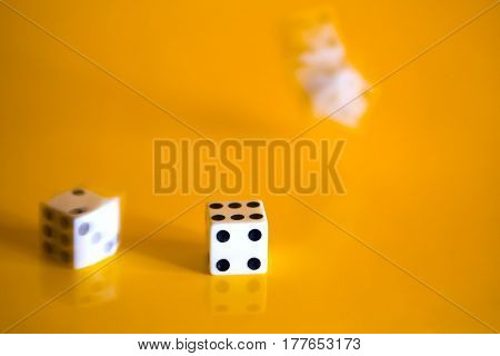 Three simple game cube cast on a bright yellow background. One cube has already stopped and two are still spinning