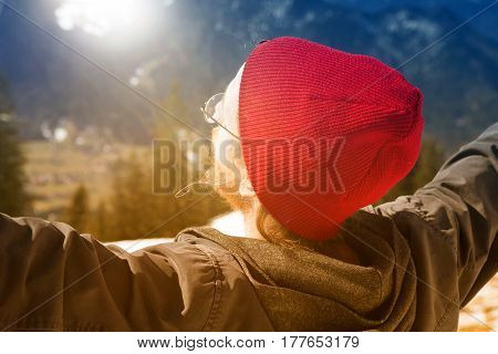 young bearded man with red cap stretching his arms towards the sun