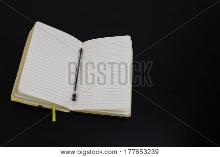 A lined notebook with pen resting on a table