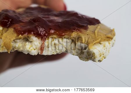 Peanut Butter and Strawberry Jelly on a Rice Cracker being eaten