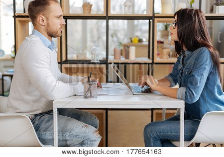 Job interview. Confident intelligent attractive businesswoman looking at the job applicant and working on the laptop while interviewing him