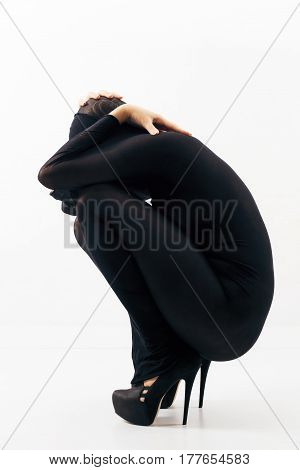 Part of series. Female nude silhouette in black nylon body stocking and in high heels shoes against white background.
