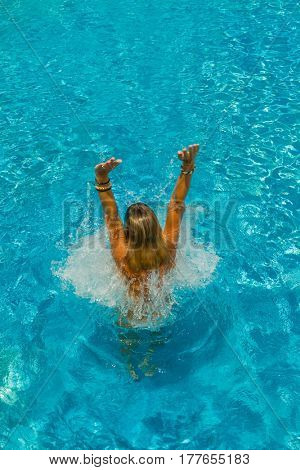Woman in the swimming pool splashing water around