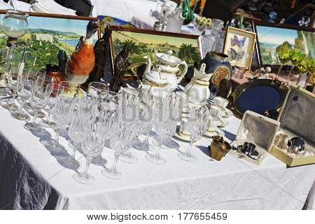 Nice France - May 17 2014: Crystal glasses and the other tableware items put on sale during the flea market which is regularly organized on one of the squares in the city