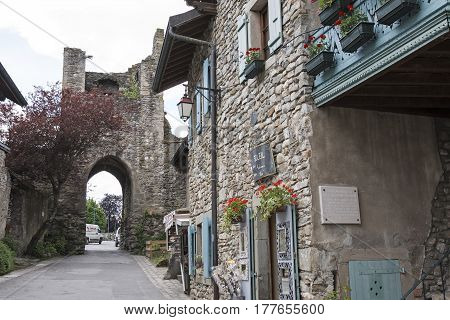 Yvoire France - May 24 2013: Narrow street leads through a gate in the damaged tower. Townhouses which were built of stone can be seen in this medieval town.