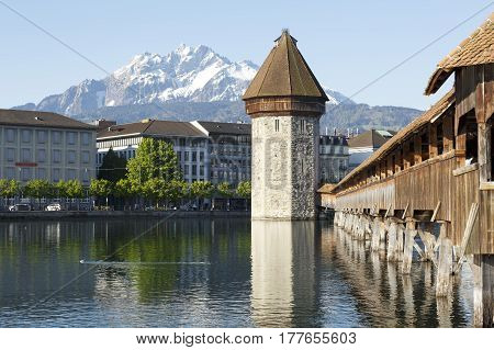 Lucerne Switzerland - May 05 2016: Octagonal tower and the Roofed Chapel Bridge by the River Reuss. Peak of Pilatus that is covered with snow can be seen in the distance