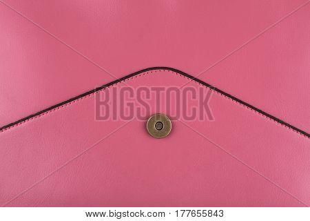 detail of pink leather envelope shape handbag with metallic enclosure