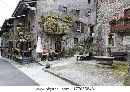 Yvoire France - May 24 2013: Townhouses which were built of stone in medieval town are located along a narrow street. In these buildings operate restaurants that are tourist attraction