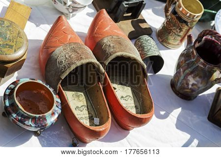 Nice France - May 17 2014: Wooden shoes commonly known as clogs on sale during the flea market which was held on one of the squares in the city. On the table the other stuff can be seen