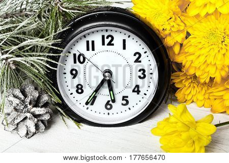 Time change - clock and flowers on wooden table