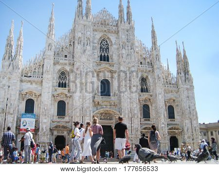 MILAN, ITALY - AUGUST 12, 2016: People in front of Piazza Duomo di Milano cathedral in Milan, Italy from the low angle. Popular travel landmark in Europe