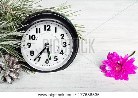 Time change - clock and winter twigs on wooden table