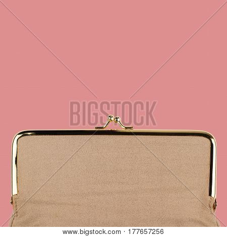 square detail of closed vintage cream colored female handbag with golden metal enclosure on pink background