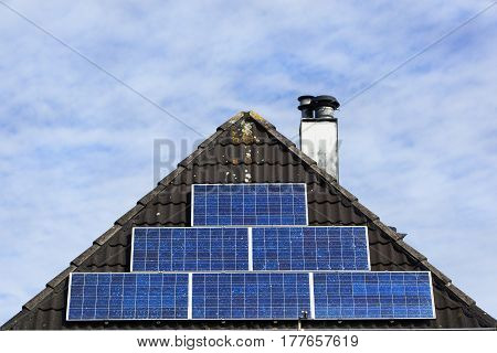 Solar panels on a tiled roof with chimney