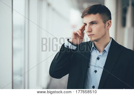 Confident Thoughtful Businessman In A Suit Holding Hand On Chin And Looking Away While Standing With
