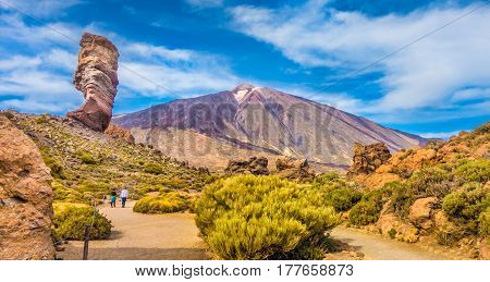 Panoramic view of unique Roque Cinchado unique rock formation with famous Pico del Teide mountain volcano summit in the background on a sunny day Teide National Park Tenerife Canary Islands Spain