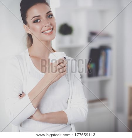 Attractive young businesswoman standing  near wall in office