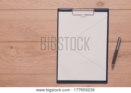 Writing, planning, schedule or checklist background. Top view of notepad with copy space on wood