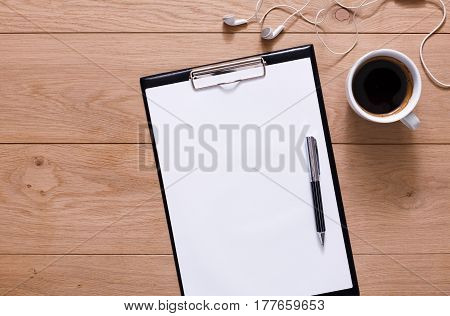 Mockup for check list, empty note paper, notepad with pen, mobile phone and coffee cup on brown wood background, top view with copy space. Office, writer or study concept