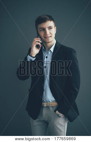 Happy Businessman Talking On The Mobile Phone Over Black Background. Looking Away