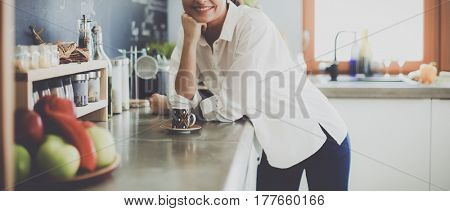 Portrait of young woman standing with arms crossed against kitchen background