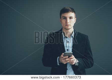 Confident Businessman Leaning Against A Wall While Using The Smartphone On Black Background