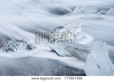 Icebergs with movement of water wave on black volcanic sand beach near Jokulsarlon glacier lagoon Southern Iceland