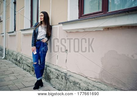 Portrait Of Stylish Young Girl Wear On Leather Jacket And Ripped Jeans With Mobile Phone At Hand. St