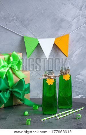 Saint Patrick's Day green party beverages glass bottles with orange paper shamrock decorations presents with ribbon bow irish flag on grey concrete background