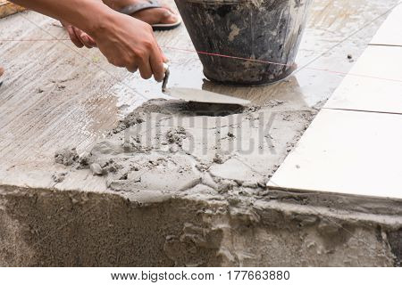 renovation - construction worker tiler is tiling ceramic tile floor adhesive.