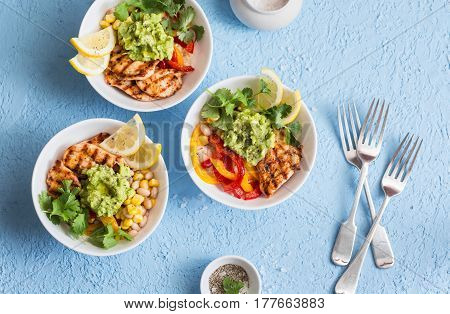 Chicken fajitas bowls on a blue background top view. Flat lay