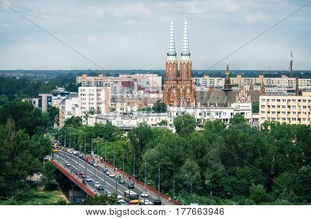 Cityscape of Warsaw Slasko-Dabrowski bridge over Vistula river on foreground Cathedral of St. Michael the Archangel and St. Florian the Martyr among buildings of Praga district on background Poland