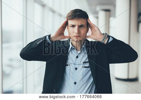 Young Man With Hands On Head Thinking In Office