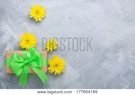 Gift Box And Yellow Chrysanthemums On Grey Concrete Background