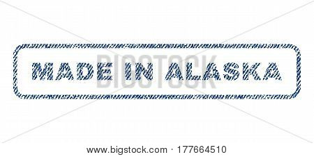 Made In Alaska text textile seal stamp watermark. Blue jeans fabric vectorized texture. Vector caption inside rounded rectangular shape. Rubber sign with fiber textile structure.