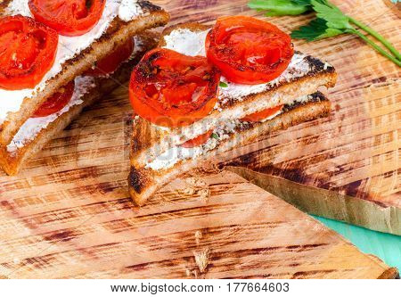 Sandwiches with fried tomatoes. On the stump surface.