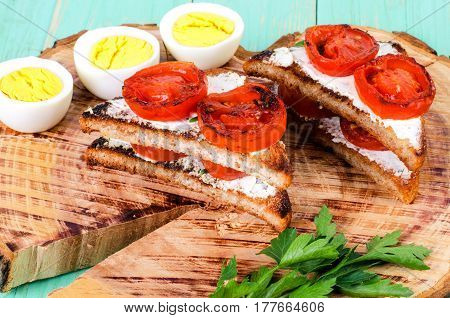 Sandwiches with fried tomatoes and boiled chopped eggs. On the stump surface.