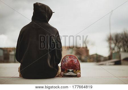Teenager sitting in a black sweatshirt holding a skateboard on a slum background