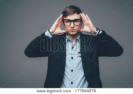 Cool Businessman With Hands On Head Standing On Grey Background