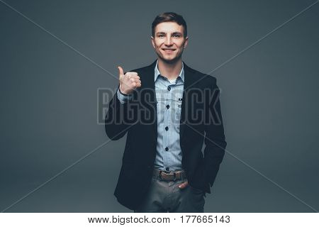 Young Handsome Businessman Pointing With Finger On Back On Grey