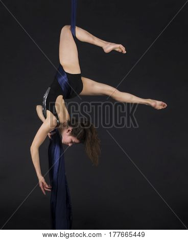 Young,smiling girl does exercises on the canvases. Studio recording of the performance on a dark background.