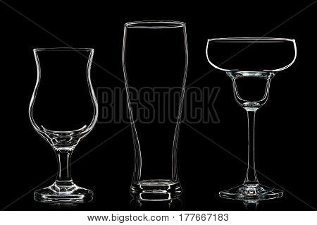 Silhouette of different glasses on black background