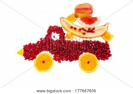 Healthy food concept with fruits. Seeds of pomegranate and slices of orange are as shape of lorry with cargo from apple orange banana and grapefruit