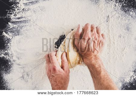 Baking concept. Hands top view knead dough on black background. Male baker